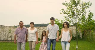 A family, with parents, children and grandparents, having fun walking in garden