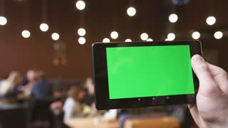 A man holds a blank tablet PC with a green screen for your own custom content.