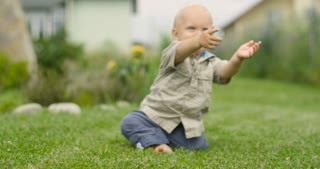 A small child sitting in the park on the green grass and looking at the camera. Slowly he gets up on its feet and begins to take the first steps