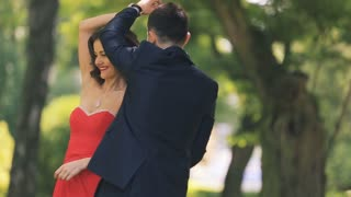A wedding couple in red dress dancing in the park in slow motion closeup