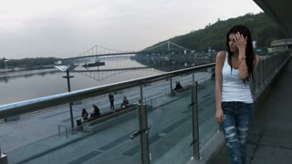 A young brunette woman in white shirt walking on a bridge in the city and is admiring the skyline
