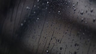 Abstract shot of rain water running down a moving car's window