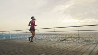 Active brunette wearing stylish sport clothes running on beautiful beach in summer.