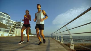 Active couple happy to have time to run together on beautiful beach.
