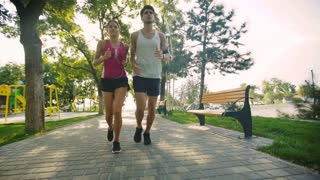 Active positive couple jogging with running watches on summer time.