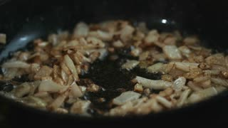 Adding sliced mushrooms to fried onions on the hot pan and stirring it closeup