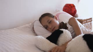 Adorable little girl resting in bed with soft toy and looking at the camera close-up