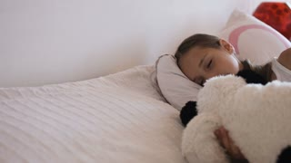 Adorable little girl sleep in the bed on sunny morning, close-up