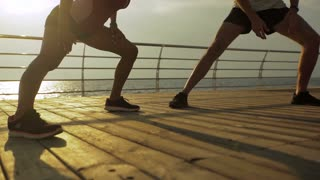 Amazing view of the sea and great couple training together on the wooden boardwalk.