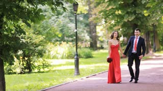 An elegant red dress wedding couple walking in the park