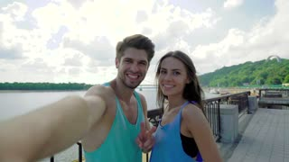 Athletic healthy cheerful couple in sportswear making selfie after training outdoors