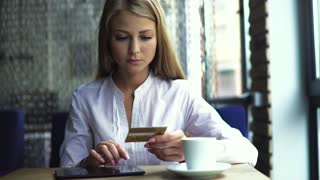 Attractive blond woman in white shirt with a credit card and a tablet computer, online shopping at café
