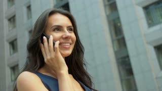 Attractive Business Woman Using Smartphone Commuter in City, Pretty Young Business Woman Talking by Phone Against Complex of Modern Office Buildings