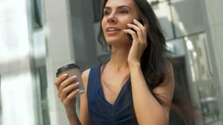 Attractive business woman walking in the city, drinking coffee and talking on a phone in the morning
