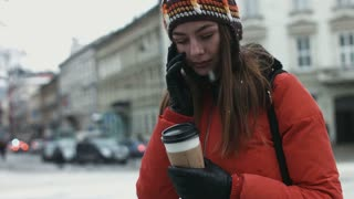 Attractive female in her 20s using cellphone outdoors. Young woman talking on telephone in the european city center.