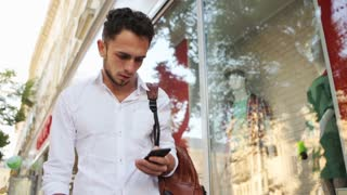 . Attractive guy using his mobile phone on the street