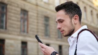 Attractive guy watching on a phone screen and smiling. Positive male in his 20s using smarphone outdoors