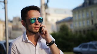 Attractive guy wearing sunglasses and talking on cellphone in the city center