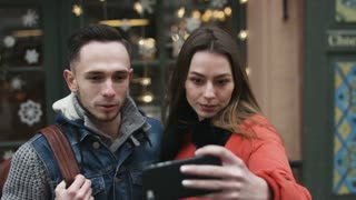 Attractive male and female in their 20s doing selfie outdoors in the city center. Couple taking pictures by using mobile device.