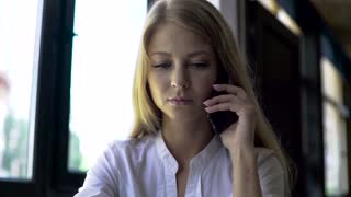 Attractive smiling blonde business woman using her phone and making notes