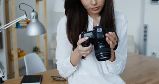 Attractive smiling brunette female photographer in white shirt checking an image holding her camera, office interior at background.