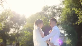 Attractive wedding couple holding by hands and whirling on the green meadow at sunset