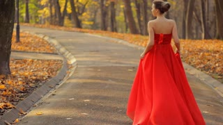 Attractive woman walking in a red long evening dress in the green summer park.