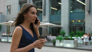 Attractive young brunette businesswoman calling on mobile phone, walking holding a cup of coffee.