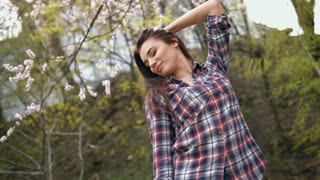 Attractive young brunette woman in checkered shirt touching hair by her hands, standing outdoors on bright sunny day in front of trees in the park