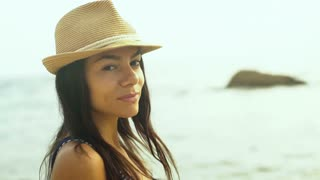 Attractive young brunette woman wearing casual clothes , smiling and posing on camera on the beach.