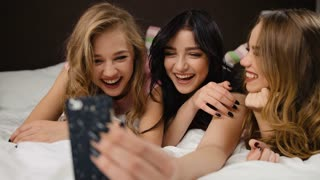 Attractive young ladies taking selfies on the bed in a modern bedroom.