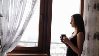 Attractive young lady having a rest and drinking a cup of tea or coffee in front of the window at home.
