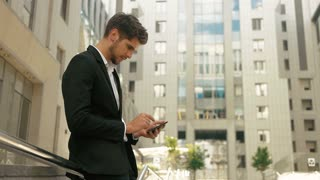 Attractive young man wearing stylish suit , using tablet in the street.