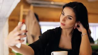 Attractive young woman wearing classical clothes taking a selfie in a fancy restaurant.