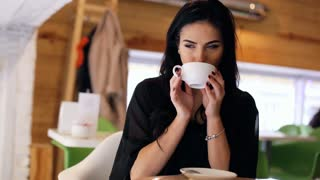 Attractive young woman with beautiful dark hair lonely drinking coffee on a cafeteria.