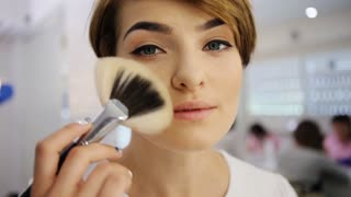 Attractivesmiling woman applying make up to her face with a brush looking at camera.