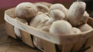 Autumn set of fresh champignons on a wooden basket left on the table at kitcken.