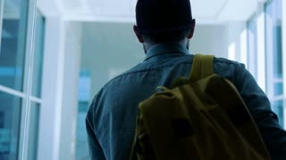 Back view of man going along hallway