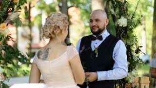 Beautiful back of bride holding a microphone telling her oath, handsome groom kissing her