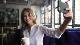 Beautiful blond woman in white shirt taking selfie holding cup in the coffee bar.