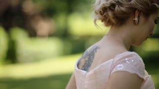 Beautiful blonde bride running in the green forest lit by sunbeams. Back view