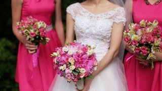 Beautiful bride standing between bridesmaids in pink dresses holding bouquets of roses
