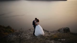 Beautiful bride wearing elegant white dress kissing her husband on the hill of mountain.