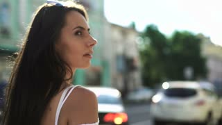 Beautiful brunette girl walks down the street of European city, looking back.