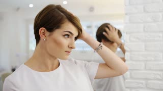 Beautiful brunette touching the ready short haircut in mirror. Concept of fashion and beauty