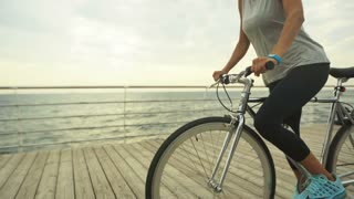 Beautiful brunette woman riding her bycicleon beautiful beach in summer.
