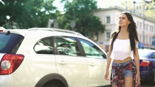 Beautiful brunette young woman wearing white shirt and jeans shorts walking on the street looking straight