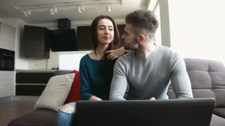 Beautiful couple sitting on a sofa, young man checking his emails in laptop and talking to girlfriend , kissing her on the lips.