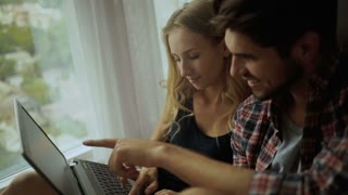 Beautiful couple working on a laptop at home.