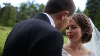 Beautiful happy brunette bride with red lips telling something to her groom standing back to the camera